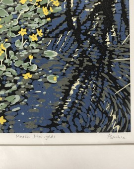 A reduction linocut of marsh marigolds next to a rippling pool of water with a reflected tree.