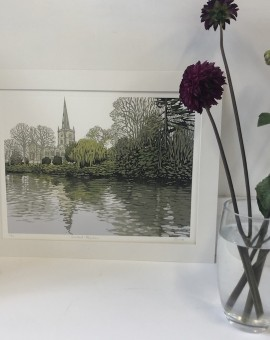 Alexandra Buckle's Stratford Reflections is a limited edition linocut print. THis piece depicts a rural scene in stratford with an intricately designed church.