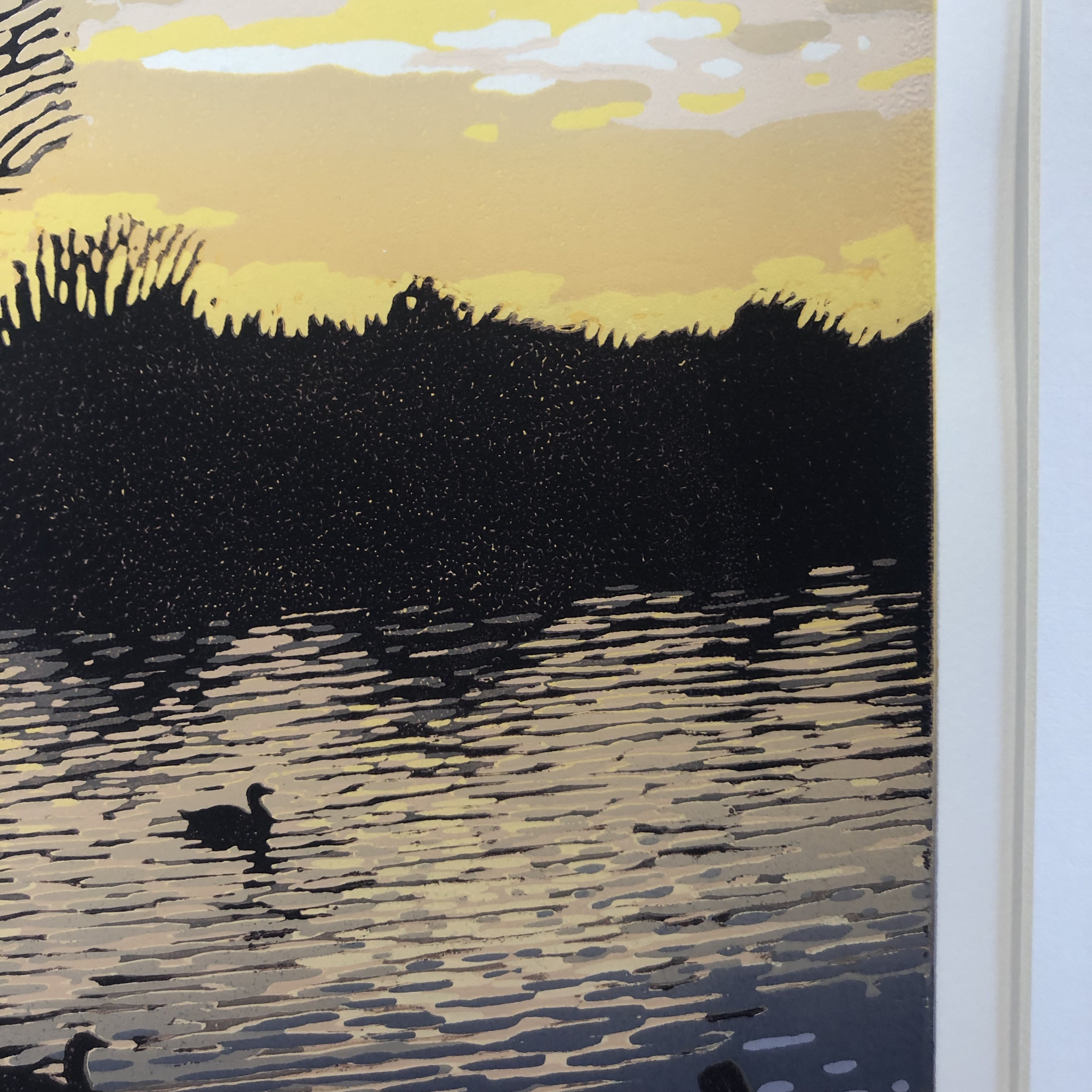 A reduction linocut of bright sunset reflecting over a wintry lake.