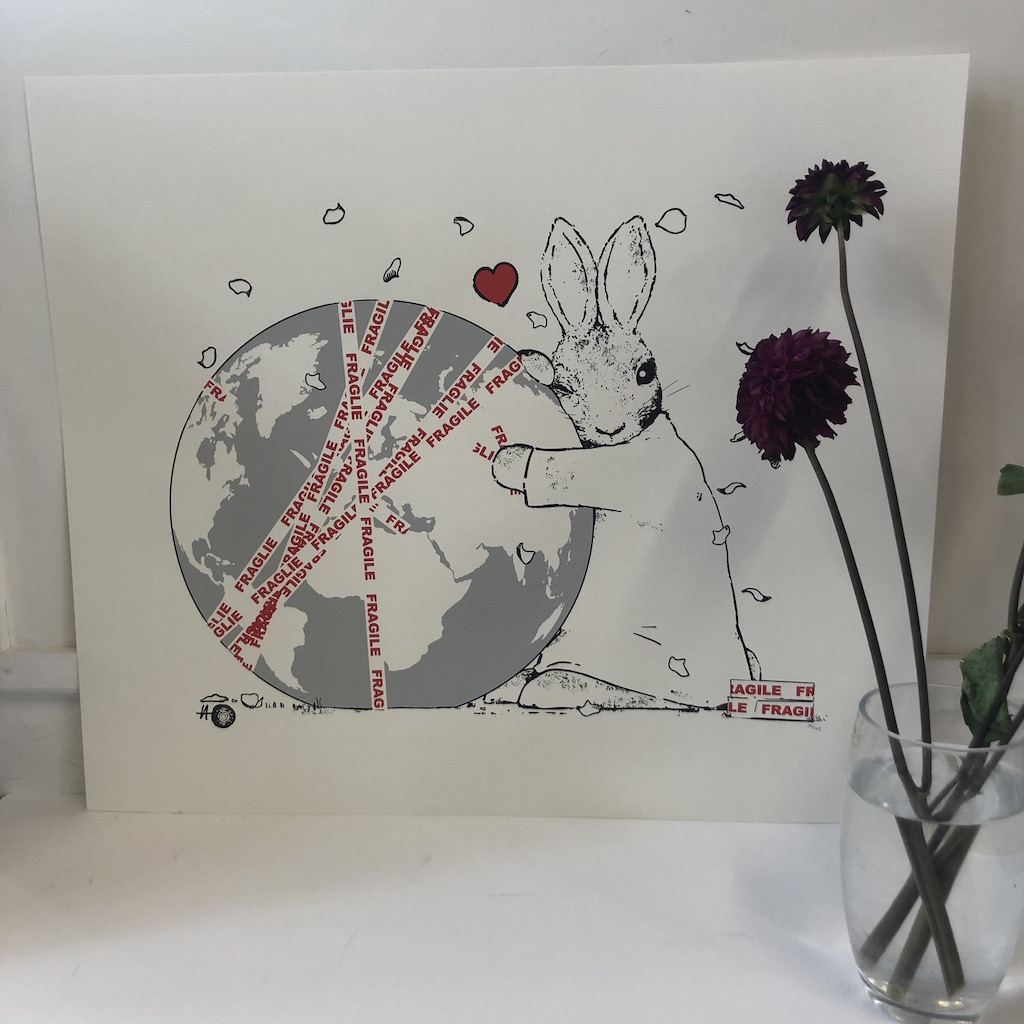 Harry Bunce's FRAGILE is a limited edition silkscreen print and depicts a rabbit hugging the globe which is wrapped in FRAGILE tape.